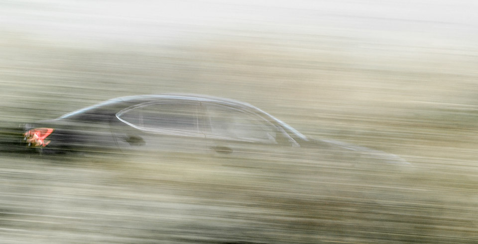 Panning shot of car passing behind hedgrow, Seven Sisters, East Sussex
