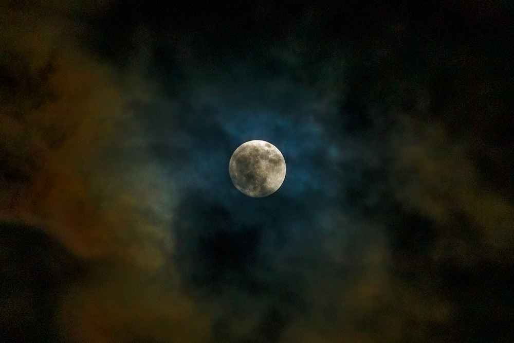 moon among clouds at night